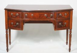 A Regency style mahogany bowfront sideboard with five drawers on reeded tapering supports,
