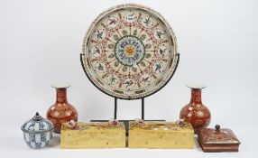 A modern pottery circular dish decorated with wild birds and butterflies on a metal stand,