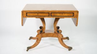 A Regency style burr walnut and ebony inlaid sofa table on four outswept supports,