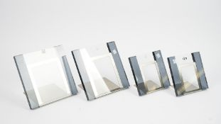 A set of four coloured glass and brushed steel photograph frames,