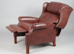 A modern hardwood framed and brown leatherette upholstered reclining wingback armchair,
