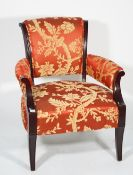 A modern ebonised hardwood low open armchair, with red and gold foliate upholstery,