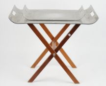 A graduated pair of aluminium twin handled trays, of contemporary form on a folding hardwood stand,