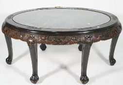 A modern Chinese carved hardwood oval coffee table, with inset glass top, 110cm wide x 50cm high.