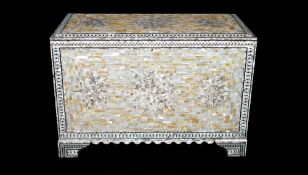A modern mother-of-pearl decorated lift top trunk on bracket feet, 90cm wide x 61cm high.