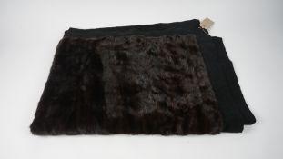 A dark brown fur throw, with black fabric border, 124cm x 167cm.