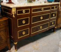 A Louis XVI style mahogany and ormolu mounted marble topped commode on fluted tapering supports,