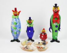 A 'Family' of four Murano coloured glass clowns and four shaped glass bowls containing a selection