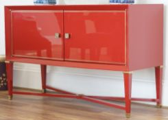 A modern red lacquer side cabinet, on tapering square supports, united by 'X' frame stretcher,
