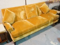 Baker; a modern three seater sofa with gold velvet upholstery, on ebonised tapering supports,