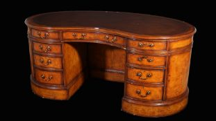 A modern mahogany kidney shaped pedestal desk with eight drawers and opposing cupboard base,