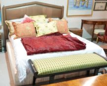 A modern kingsize bed with faux metallic green studded upholstered headboard,