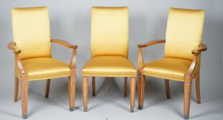Linley; a set of twelve gold silk upholstered walnut dining chairs on silver plated capped supports,