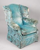 A modern wingback armchair with rollover arms and turquoise and silver foliate upholstery,