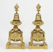 A pair of Louis XVI style gilt metal chenets, modern, each with flaming urn finial,