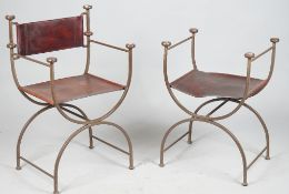 A set of four wrought iron and brown leather open armchairs with 'X' frame supports,