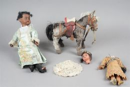 A German bisque head doll, black face, glass eyes and open mouth with jointed wooden limbs,