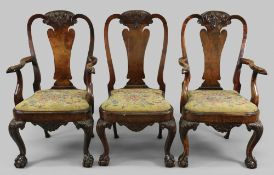 A pair of George I style carved walnut a