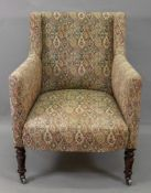 An early Victorian upholstered armchair, on grained faux rosewood legs and castors.