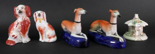 A pair of late Staffordshire recumbent greyhound quill holders, 16cm wide,