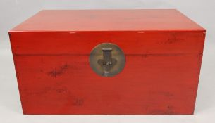 A Chinese red lacquered rectangular trunk, 20th century, with hinged top,