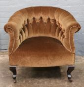 An Edwardian button down upholstered tub back armchair on cabriole legs.