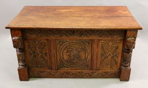 A reproduction foliate carved oak coffer, in 17th century style, of panelled construction,