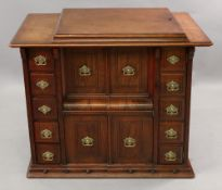 A Singer sewing machine in walnut cabinet, fitted with drawers and cupboards,