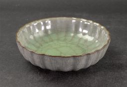A Chinese Guan-style bowl, covered in a crackled celadon glaze, notched rim, 15.5cm diameter.