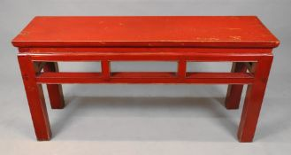 A Chinese red lacquered low table, with a rectangular top, on rectangular section legs,