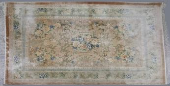 A modern silk rug, with a floral design within a border, on a cream ground, 246 x 169cm.