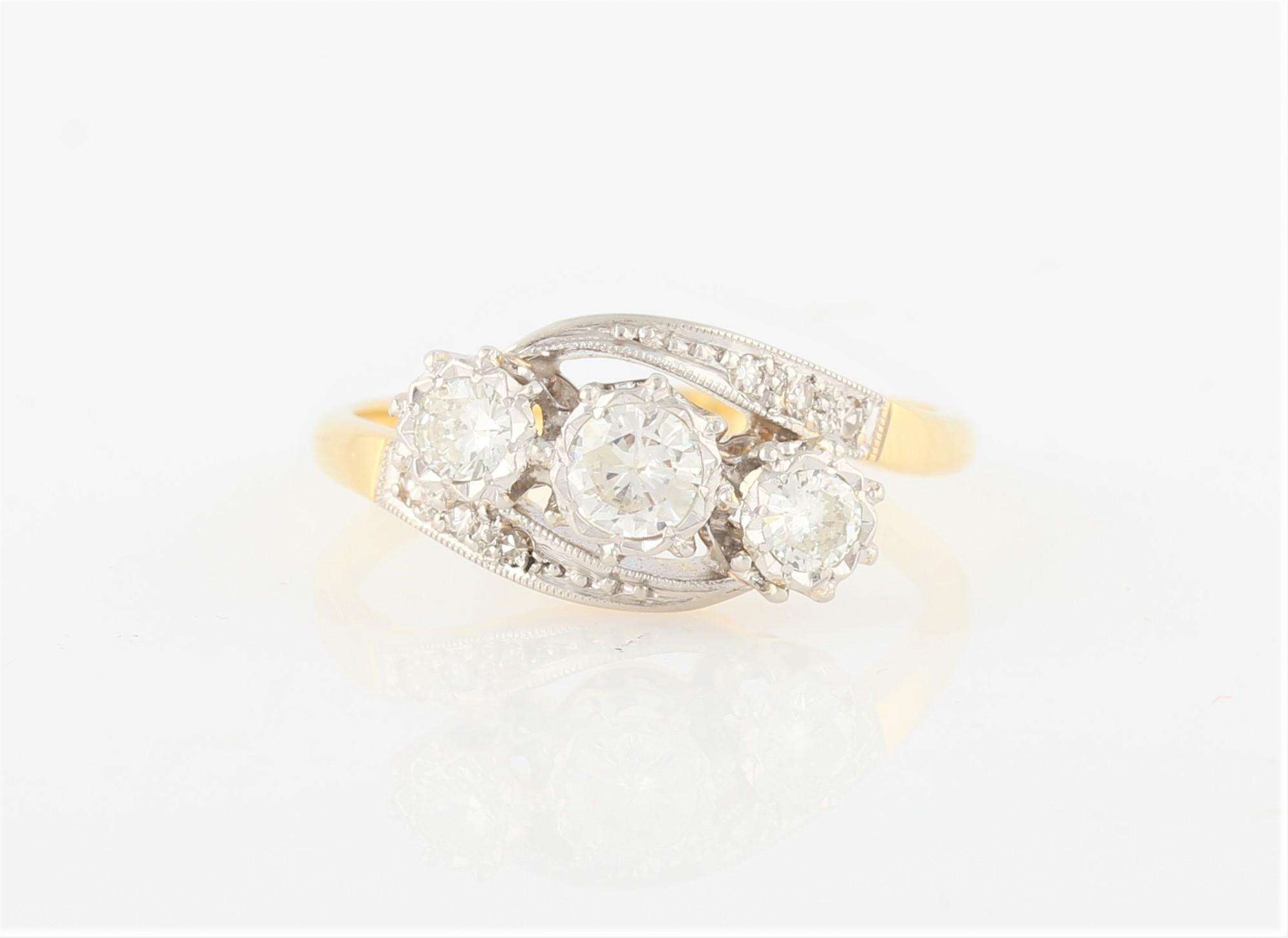Lot 48 - A three stone diamond ring, set with three graduated round brilliant cut diamonds in cross over