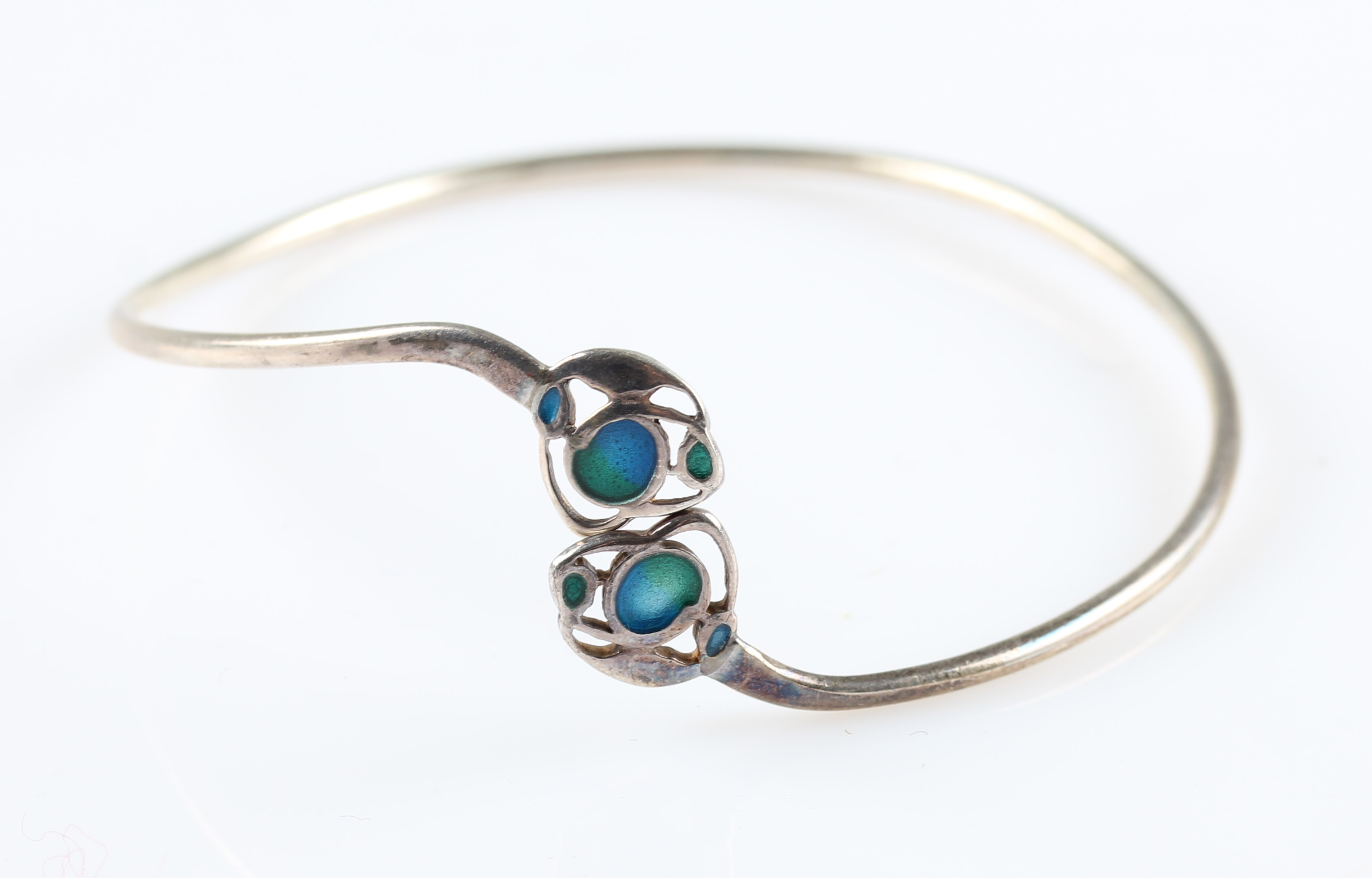 Lot 5 - A Liberty & Co. silver and enamel bangle, the Arts & Crafts style cross over design featuring two