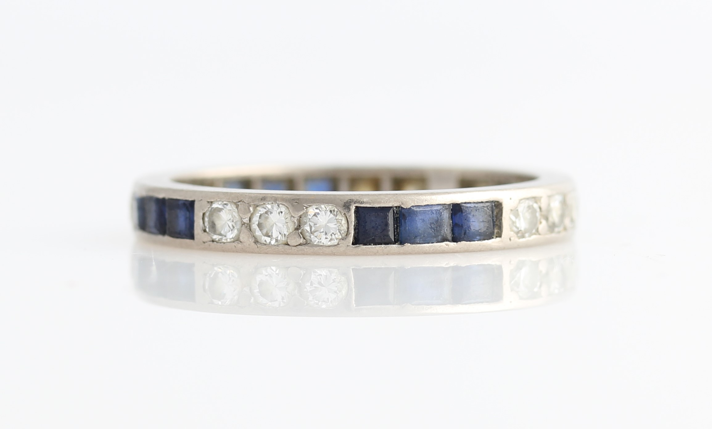 Lot 37 - A diamond and sapphire full eternity ring, set alternately with three square cut sapphires and three