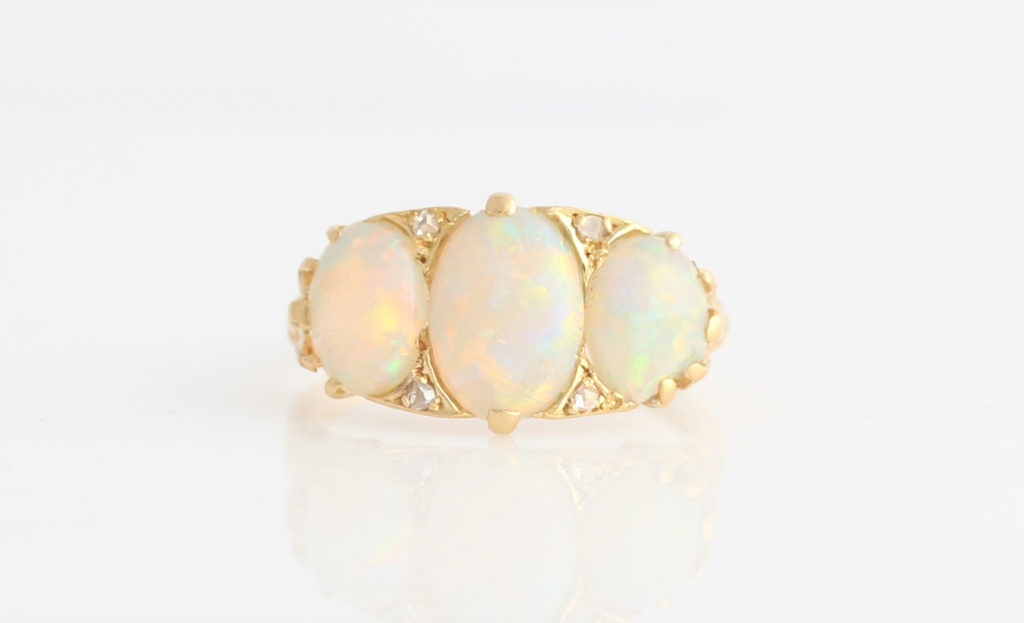 Lot 49 - An opal and diamond ring, set with three graduated oval opal cabochons separated by four rose cut