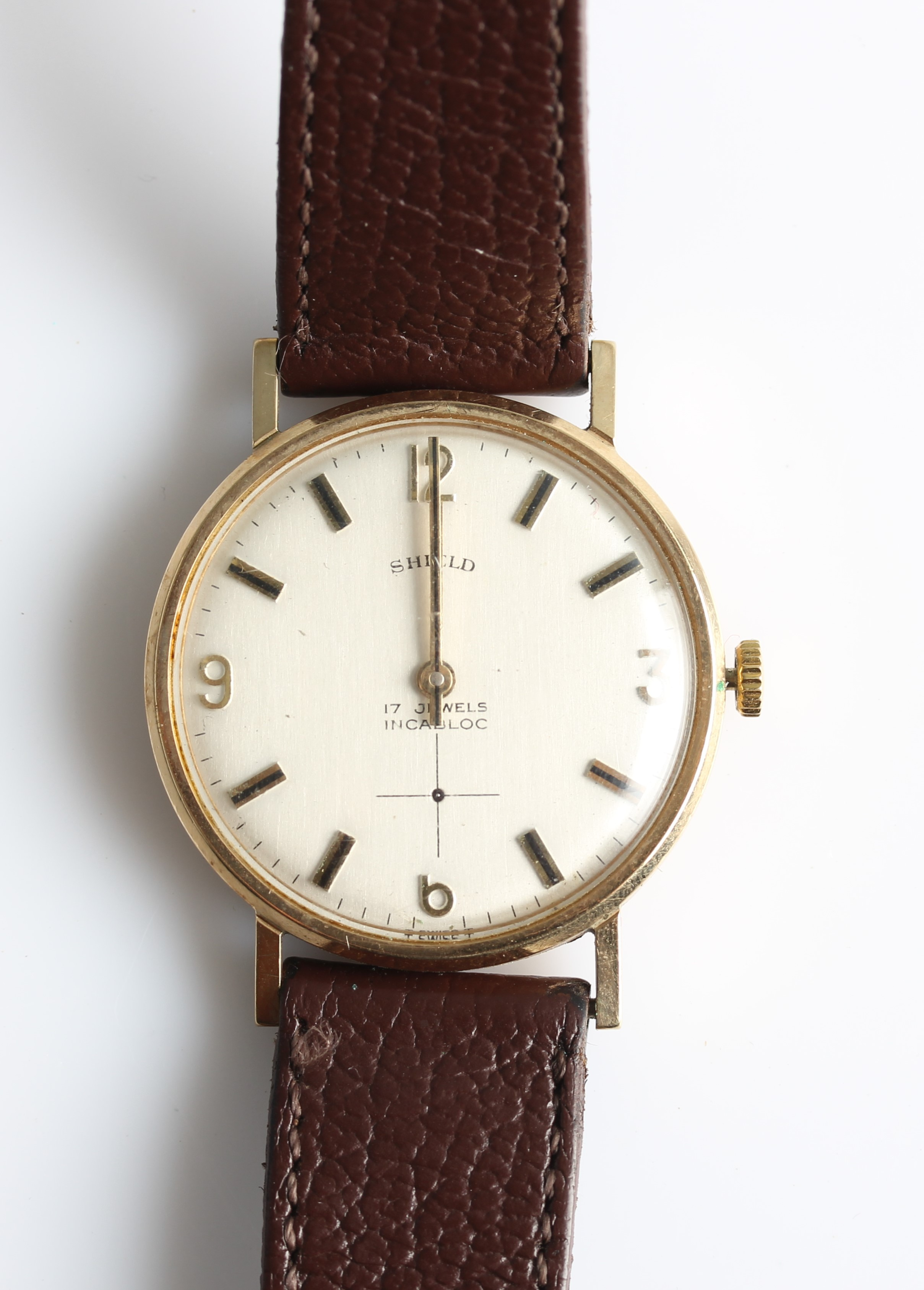 Lot 30 - A 9ct yellow gold gents Shield wrist watch, the silver-tone dial having hourly baton markers and