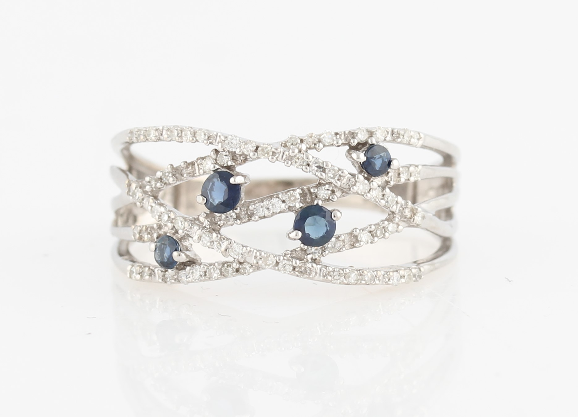 Lot 51 - A sapphire and diamond band ring, the open metalwork cross over design set with eight-cut diamond