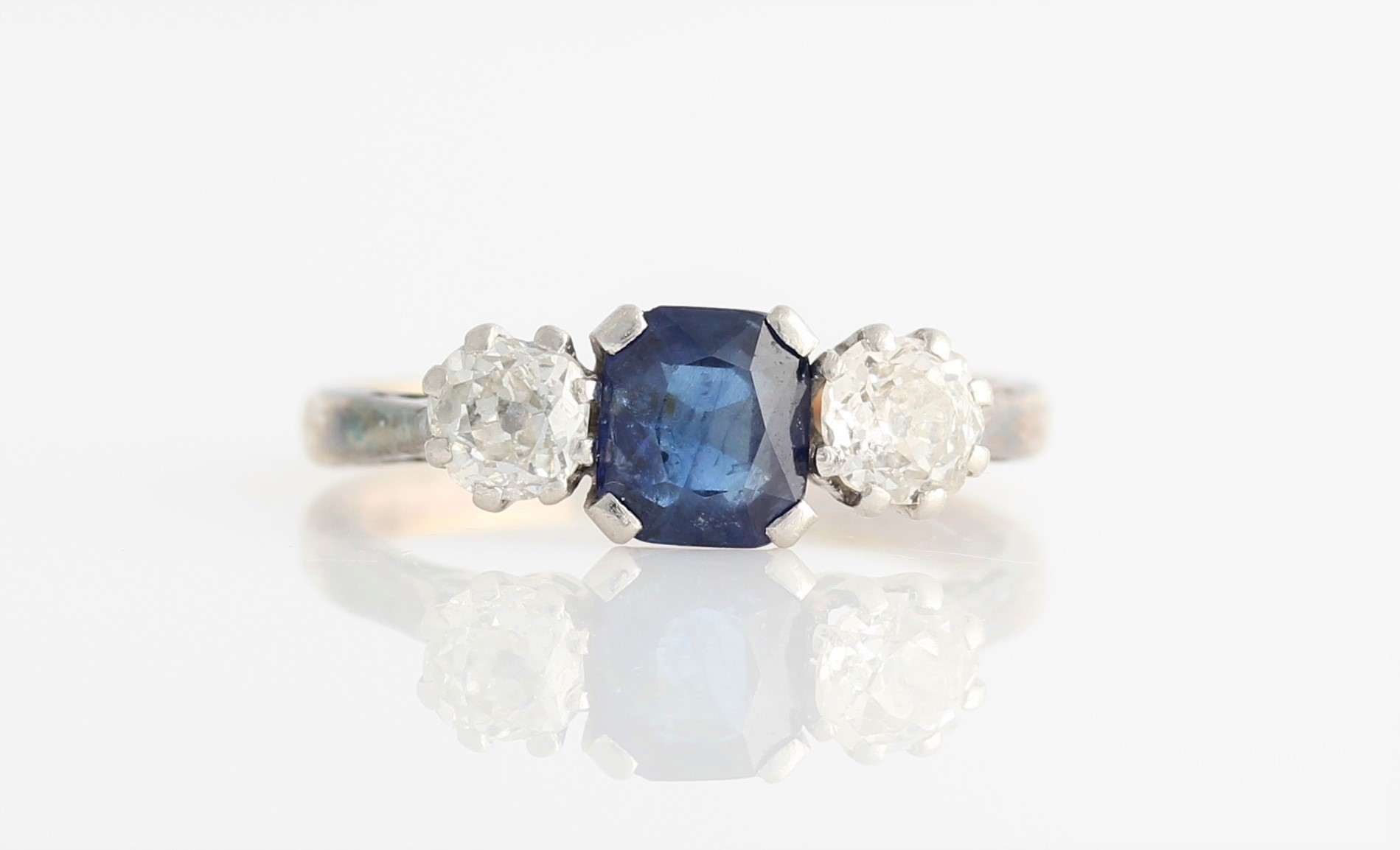Lot 44 - A sapphire and diamond three stone ring, set with a central square cut sapphire, flanked to either