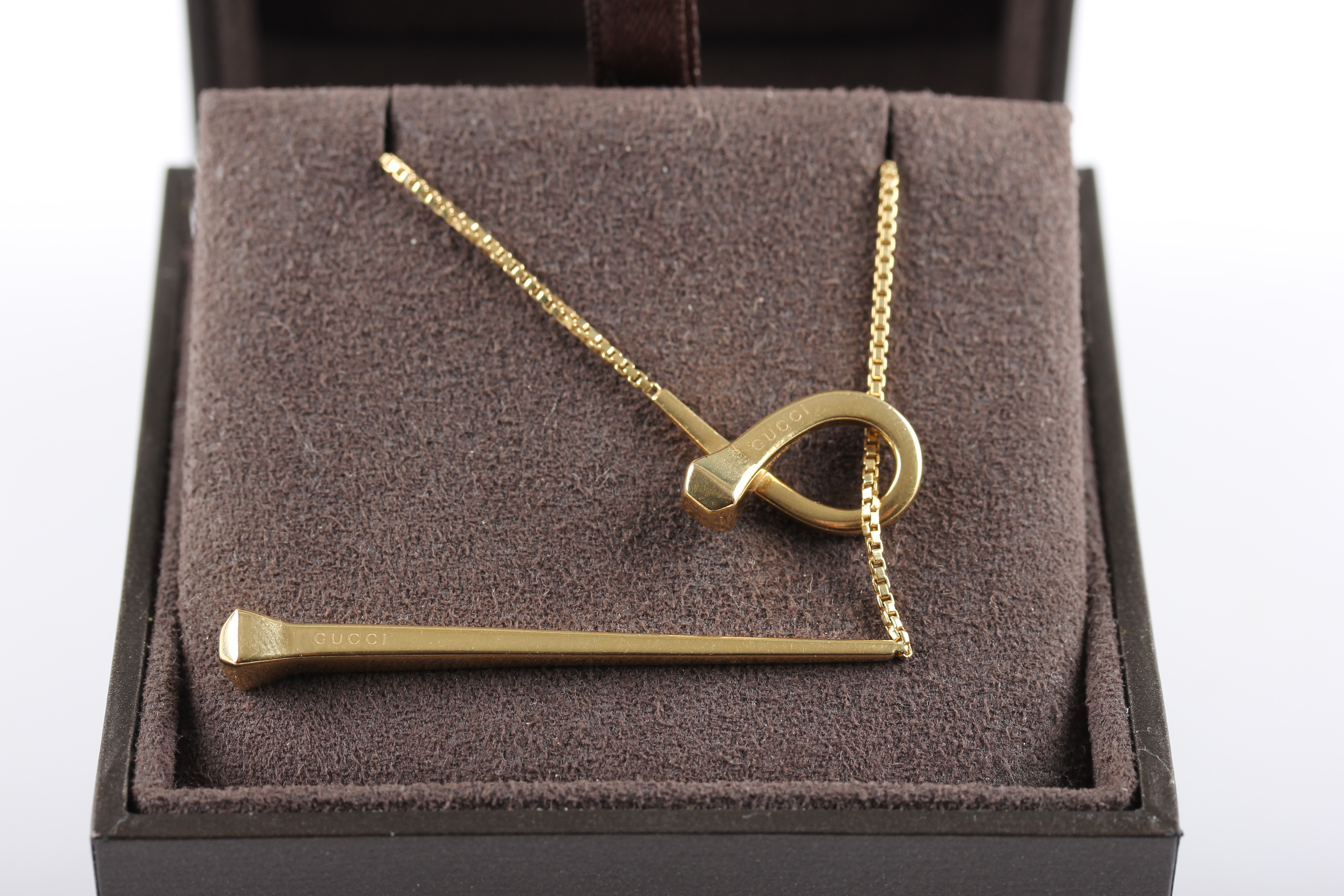 Lot 13 - A hallmarked 18ct yellow gold Gucci necklet, the tapered bar and loop design stamped GUCCI, housed