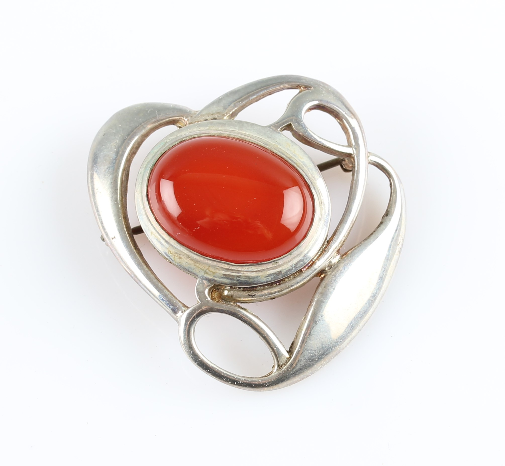 Lot 8 - A Liberty & Co. silver carnelian brooch, the open metalwork Arts & Crafts design set centrally