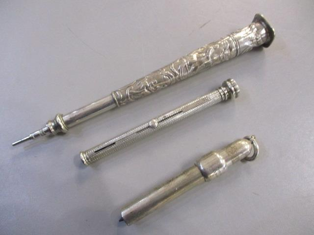 Lot 46 - Three Morden & Co silver retractable pencils, one embossed with figures and scrolls, one with engine