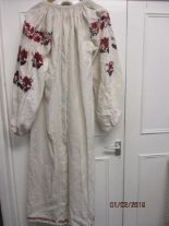 Lot 60 - A 19th century Russian traditional dress with embroidered red flowers to the shoulders, sleeves