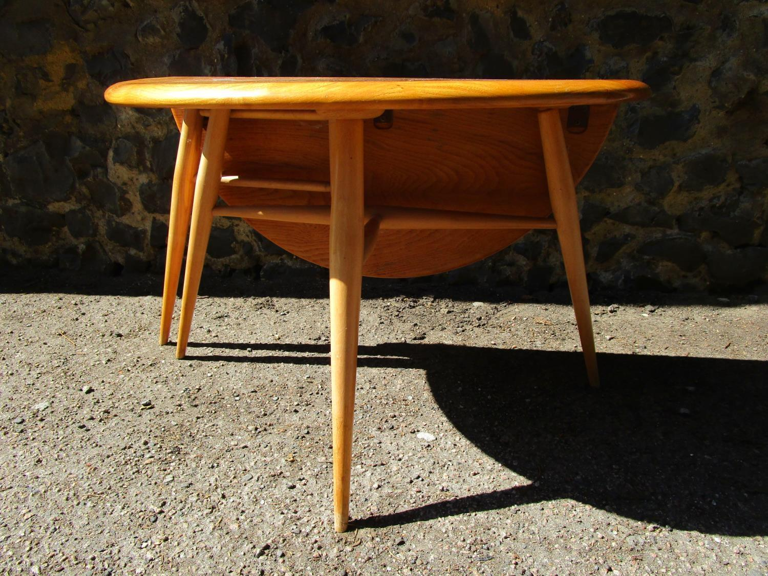 An Ercol small half moon drop flap coffee table in beech and walnut design 308, blue and gold Erc