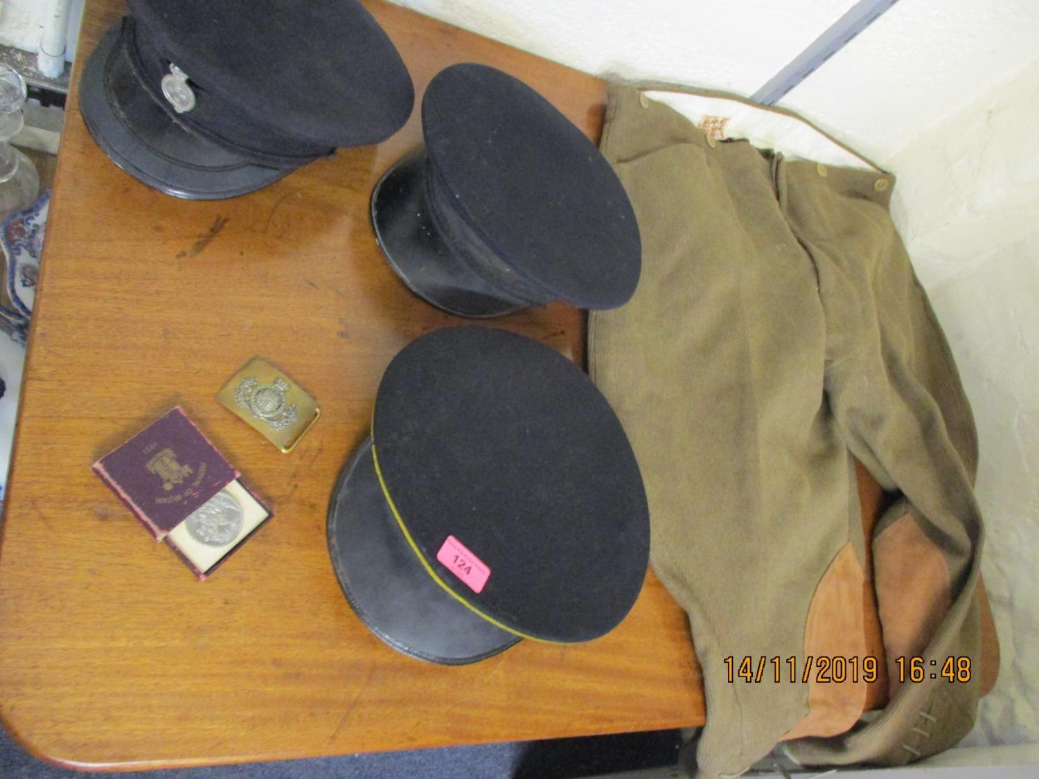 Lot 124 - Military related items to include three caps with badges, jodhpurs, a belt buckle and other badges