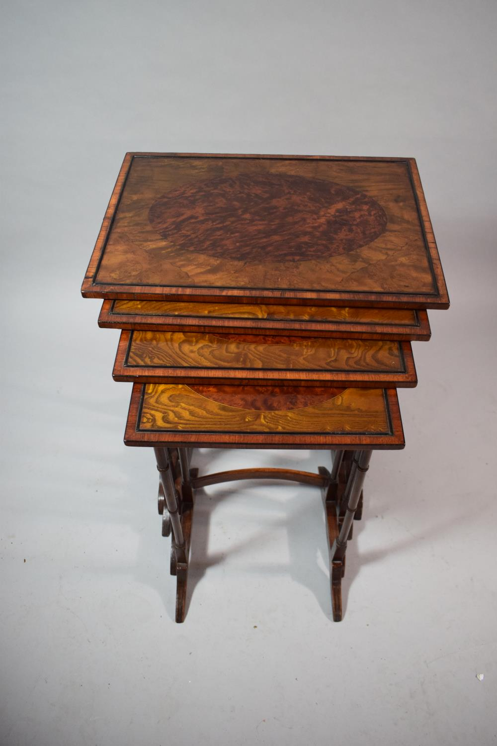 Lot 10 - An Inlaid Walnut Quartetto of Tables with Spindle Supports and Burr Oval Tops Largest 50cms Wide
