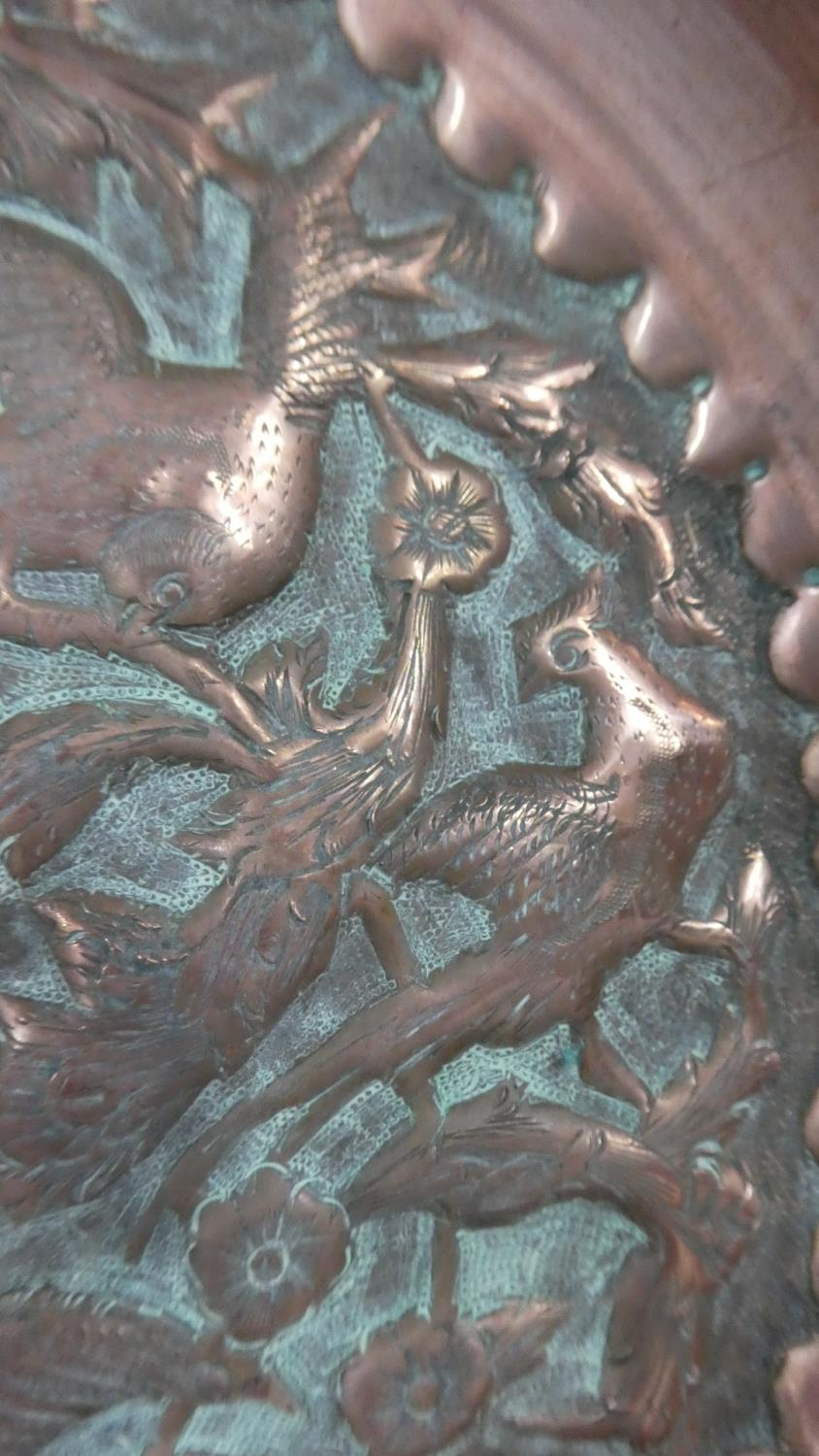 Lot 14 - An Arts and Crafts Style Copper Dish decorated in relief with Birds and Foliage. 22cms Diameter