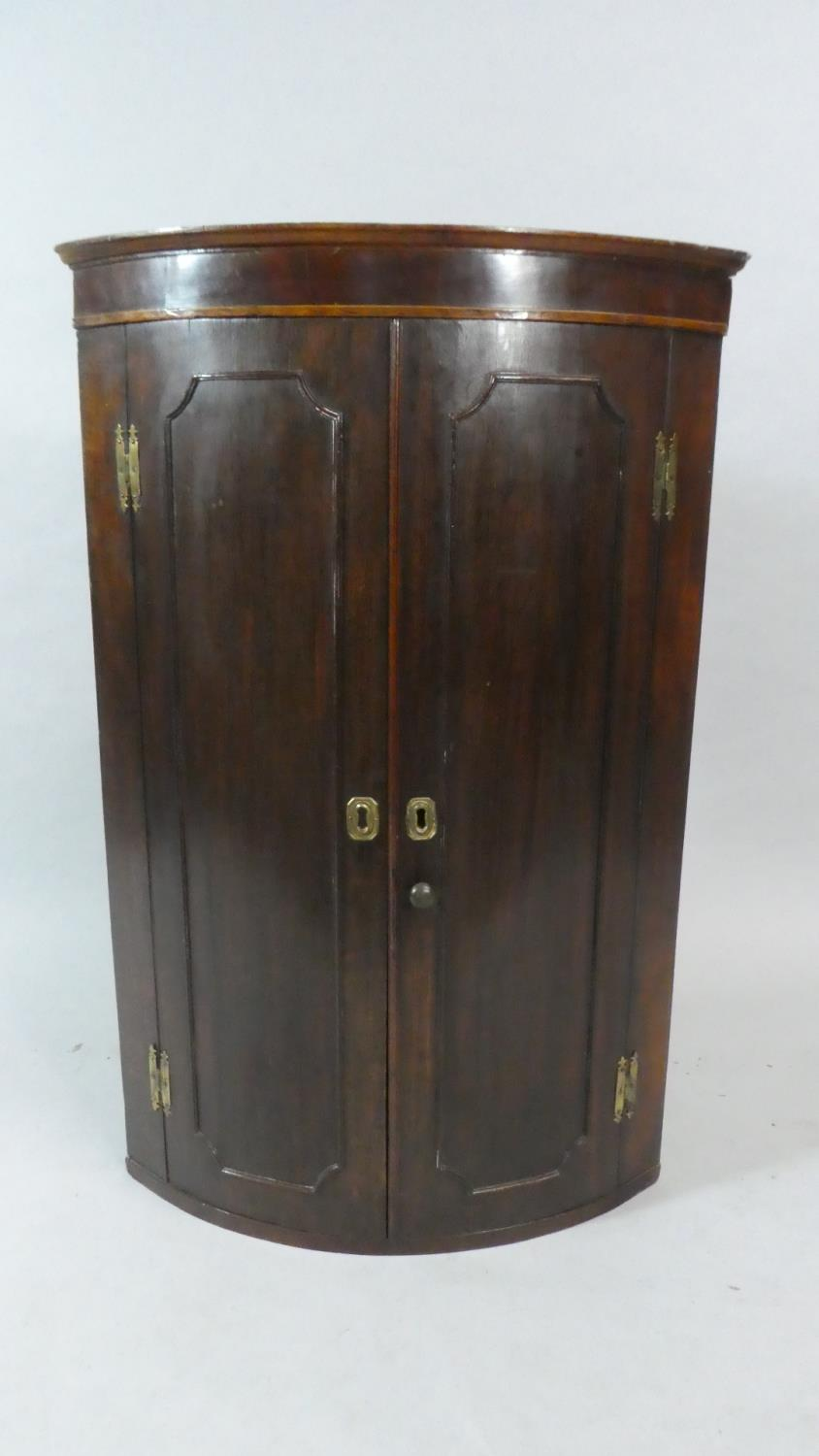 Lot 436 - A 19th Century Bow Fronted Mahogany Wall Hanging Corner Cabinet. 66cms