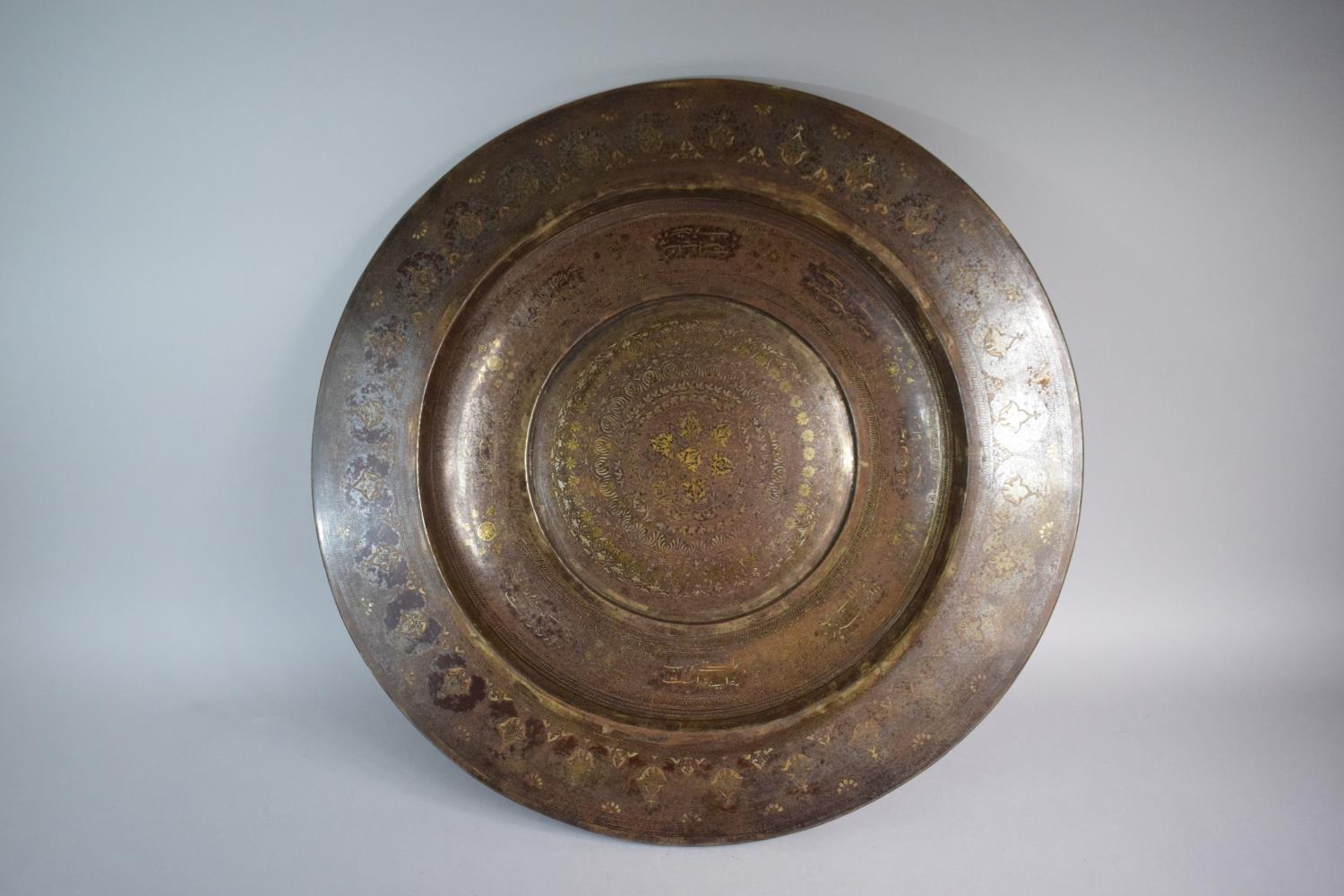 Lot 114 - A North Indian or Persian Qajar Metal Charger with Geometric and Islamic Decoration some in Gold and