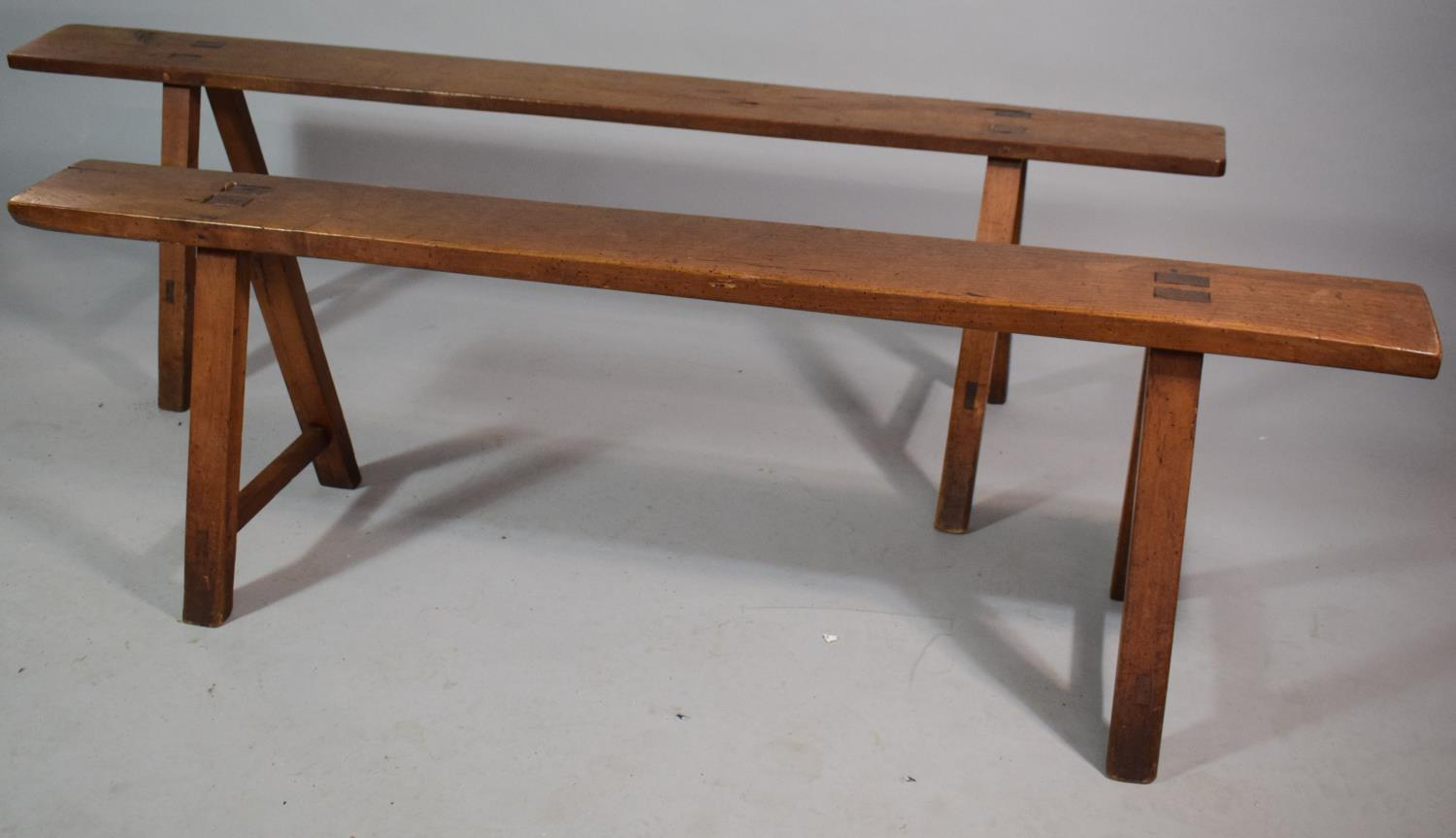 Lot 450 - A Pair of Vintage French Fruit Wood Benches on 'A' Frame Supports. 161ms and 144cms Long