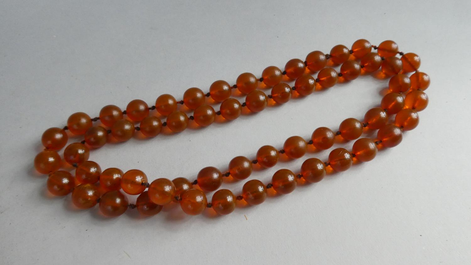Lot 340 - A Long String of Orange Amber Spherical Beads, 59 in total, Each Approx 1.5cms Diameter on Knotted
